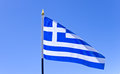 National flag of greece on flagpole over blue sky Stock Photo