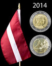 National flag of latvia and euro coin with latvian avers revers isolated on black Stock Photography