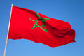National flag of morocco on a flagpole above clear blue sky Stock Photo