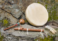 Native american drum with flute and shaker large flat decorative feathers a hand carved against a natural stone backdrop Royalty Free Stock Photos