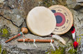 Native american drums flute and shaker two against a natural stone background Stock Photos