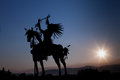 Native american silhouette with sun a of a on a horse made from metal eight rays emanating out from the setting in the distance Stock Image