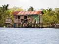 Native home rustic amerindian house on stilts over the water with coconut trees in background archipelago of bocas del toro panama Royalty Free Stock Photos