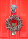 Natural christmas wreath hanging from an ornate knocker on a bright red door Stock Image