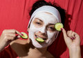 Natural face care young woman having a white smoothing mask and cucumber Royalty Free Stock Photo