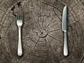 Natural food concept and organic eating healthy lifestyle idea with a silver fork and knife on a cut tree stump log representing Royalty Free Stock Images