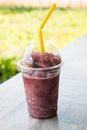 Natural grape smoothie and straw in plastic cup Royalty Free Stock Photo