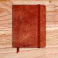 Natural leather notebook on a wooden desk copybook with band and bookmark vector Royalty Free Stock Photo