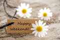 Natural looking label with happy weekend a on it and white flowers in the background Stock Images