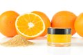 Natural orange sugar lip scrub on white background cosmetic in a glass jar with oranges in a background Stock Photo
