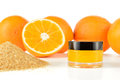 Natural orange sugar lip scrub on white background cosmetic in a glass jar with oranges and in a background Stock Images