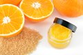 Natural orange sugar lip scrub on white. Royalty Free Stock Photo