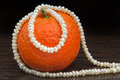 Natural pearls necklace and mandarin rolled around an orange tangerine put on a wooden teak table Stock Photography