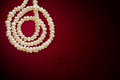 Natural pearls necklace in spiral on a red background with space for copy text Stock Photography