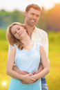 Natural portrait of happy romantic caucasian couple standing tog together and embracing outdoors in park vertical image Stock Photos