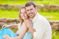 Natural portrait of young caucasian couple sitting together outd outdoors and embracing horizontal image composition Royalty Free Stock Photo