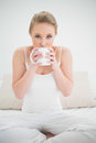 Natural pretty blonde drinking from a mug in bright bedroom Royalty Free Stock Photos