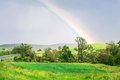 Natural rainbow over beautiful green landscape fiel field of spring grass and forest in romania Stock Photos