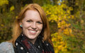Natural red-haired young smiling woman in autumn on a walk. Royalty Free Stock Photo