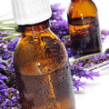 Natural remedies closeup of some dropper bottles with and a pile of lavender flowers on a white background Stock Images