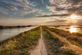 Natural reserve panorama at sunset of the wetland a long straight path across the lagoon in the valli di comacchio in italy Royalty Free Stock Images