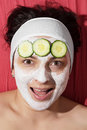 Natural skin care young caucasian having a white smoothing face mask and cucumber Stock Photos