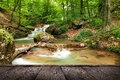 Natural spring waterfall the beautiful in forest long exposure and wood pier Royalty Free Stock Photo