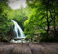 Natural spring waterfall the beautiful in forest and wood pier long exposure Royalty Free Stock Photo