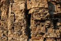 Close-up rufous stony wall with layered uneven hollowed-out surface. Royalty Free Stock Photo