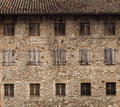 Natural stone facade of an old rural house with three files of windows, Royalty Free Stock Photo