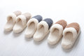 Natural woollen slippers three pair of on wooden floor Stock Photos