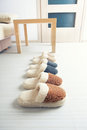 Natural woollen slippers three pair of on wooden floor in room Royalty Free Stock Images