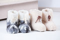 Natural woollen slippers two pair of on wooden floor Stock Image