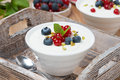 Natural yogurt with fresh berries on a wooden tray close up Stock Photo