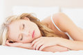 Natural young blonde lying on her bed asleep at home in the bedroom Royalty Free Stock Photos