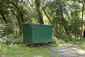 Nature dumpster a green metal trash in front of some trees Stock Images