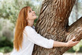 Nature lover concept with a beautiful young girl standing embracing a tree trunk with a smile of pleasure Stock Photography
