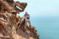 Nature photographer scrambles on rock while traveling, Hormuz Is