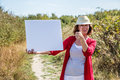 Nature teasing for smiling s woman agreeing to message with summer hat on white blank panel walking on countryside path Royalty Free Stock Photos