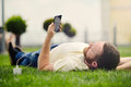 Nature and technology. A man with a beard lies on a green grass with a smartphone in his hands is charging power bank. Royalty Free Stock Photo
