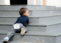 Naughty baby lying on the stairs outdoor Royalty Free Stock Photo