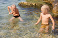 Naughty boy and girl playing in water Royalty Free Stock Photos