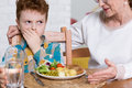 Naughty boy and healthy dinner young refusing to eat with vegetables next to him his grandmother Stock Image