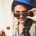 Naughty funky girl sucking lollipop young sexy woman in blue cap and jeans jacket looking at camera through sunglasses outdoors Royalty Free Stock Photo