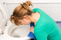 Nausea woman vomits in to the toilet Stock Photos