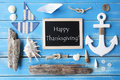 Nautic chalkboard and text happy thanksgiving flat lay of on blue wooden background or maritime summer decoration as holiday Stock Photos