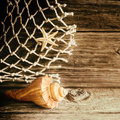 Nautical background with a shell and starfish rustic piece of natural fibre fishing net on an old weathered knotty wooden Stock Photo