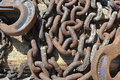 Nautical chain links  and clips rusted and weathered textured metal resting on a seaside dock detail Royalty Free Stock Photo