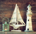 Nautical lifestyle evening concept. old vintage lighthouse, sailing boat and lantern on wooden table. vintage filtered image Royalty Free Stock Photo
