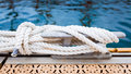 Nautical mooring rope close up of a with a knotted end tied around a cleat on a pier Royalty Free Stock Photo